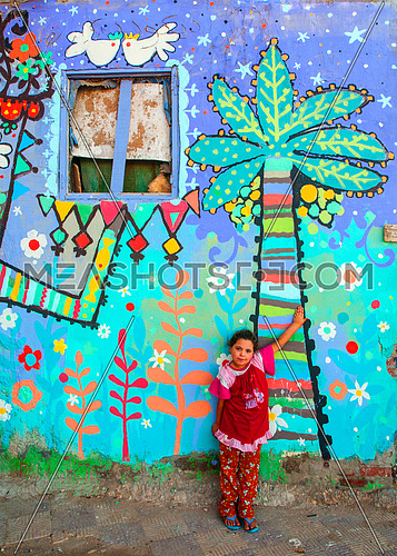 a girl standing in front of a wall painted with palm trees