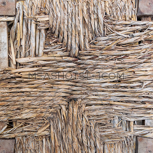Weathered part of natural thatched wall of old countryside building