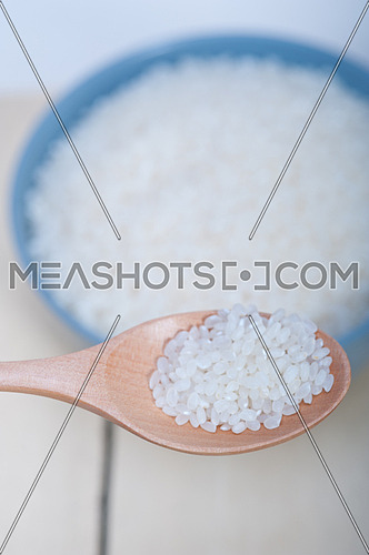 raw white rice on wood spoon and blue bowl extreme close up