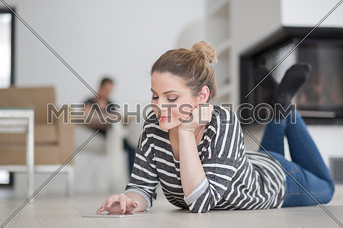 beautiful young woman websurfing using tablet computer on the floor in front of fireplace on cold winter day at home