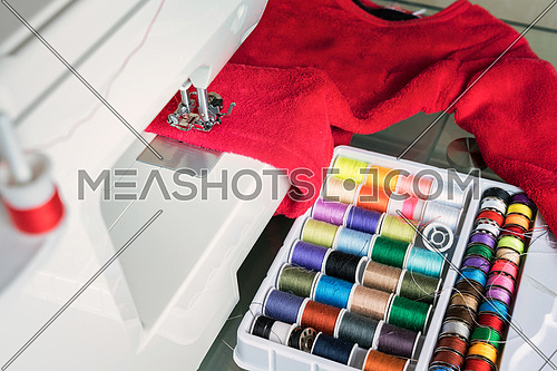 sewing machine and red cloth, sewing process in the phase of overstitching,colored spools.