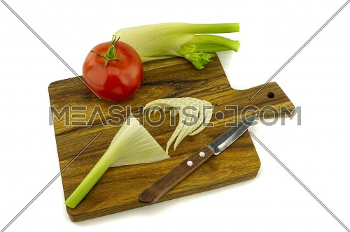 Preparing fresh vegetables and salad greens slicing them on a wooden cutting board over a white background in a healthy diet and nutrition concept
