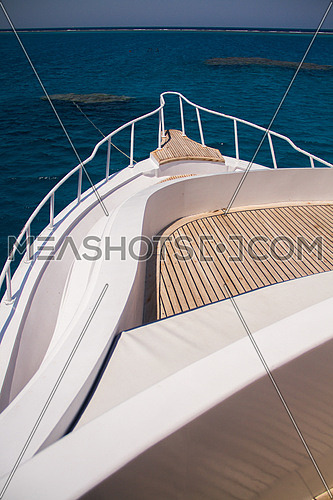 the front section of a live a board marine vessel boat showing the wooden deck