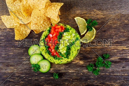Homemade guacamole with corn tortilla chips and vegetables overhead view