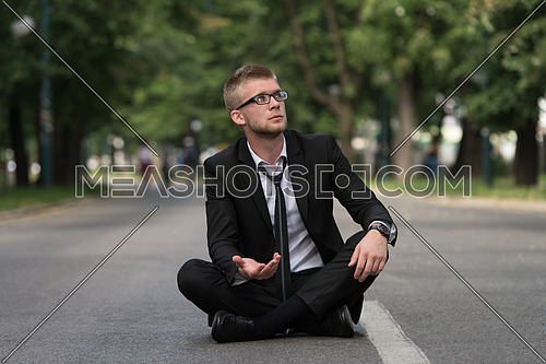 Young Businessman Sitting on Asphalt Begs For Money Outdoors In Park