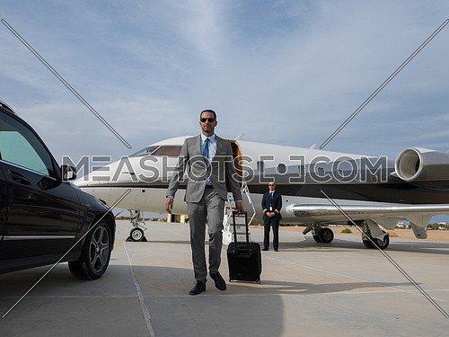 young successful middle eastern businessman with a suitcase walking in front of private airplane