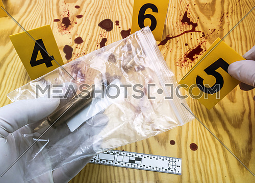 scene of crime, Scientific police picking up bullet cap in evidence bag, rule of ballistic measurement, conceptual image, horizontal composition
