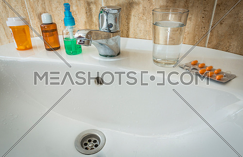 Washbasin with several bottles of medicine and a glass of water