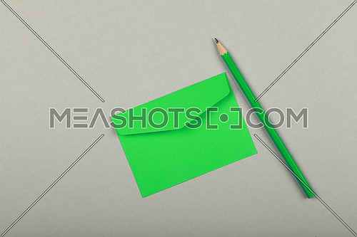 One closed blank pastel green paper envelope and wooden pencil over grey background, flat lay, directly above
