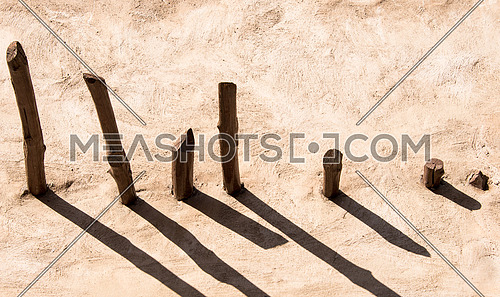 abstract wooden pillers coming out of a concreat wall