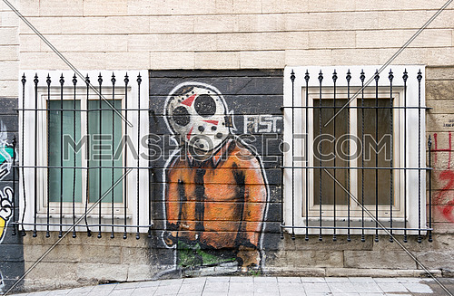 Istanbul, Turkey - April 18, 2017:  Beige bricks external wall with graffiti drawing between two windows near Istiklal Street