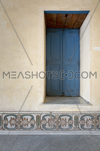 Vintage blue wooden recessed window of a old historic building with vintage plaster wall, Medieval Cairo, Egypt