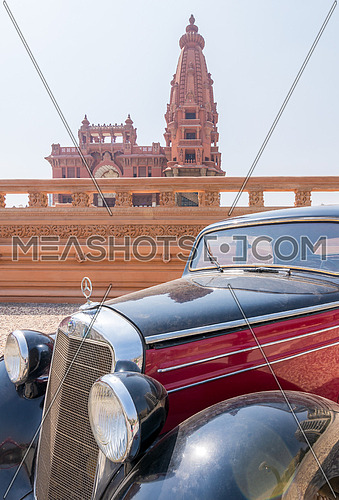 1953 Black and red Mercedes antique car, with Baron Empain Palace in the far end, Heliopolis district, Cairo, Egypt