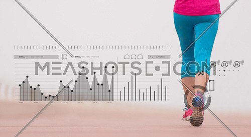 very active young beautiful woman busy running on the promenade along the ocean side to keep up her fitness levels as much as possible