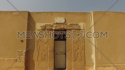 Tilt Down for an ancient Pharaonic temple door at Saqqara area at day.