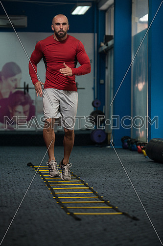 Handsome Man Running On Step Ladders Lying On Floor - Sports And Fitness - Concept Of Healthy Lifestyle - Fitness Male