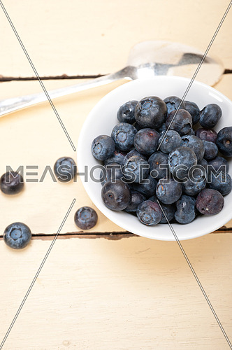 fresh blueberry on a bowl with silver spoon over wood table