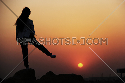 A girl in silhouette standing on a rock looking towards sunset