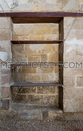 Recessed frame (Niche) with wooden shelves in an old weathered stone bricks wall, Medieval Cairo, Egypt