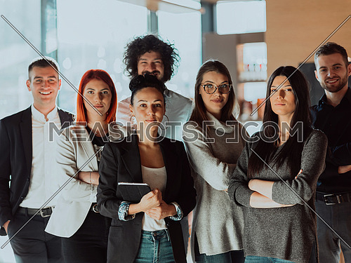 Portrait of successful group of business people at modern office. Happy businessmen and satisfied businesswomen standing as a team in office. Successful group of people smiling and looking at camera.