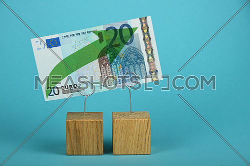 Growth and support of European economy and Euro, twenty Euro banknote with green arrow up on two holders over blue background
