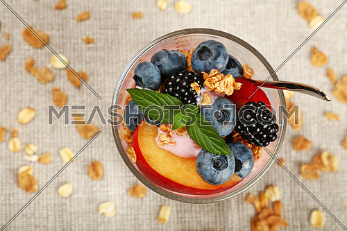 Close up portion of muesli granola breakfast with yogurt in glass, fruits and berries, elevated top view, directly above