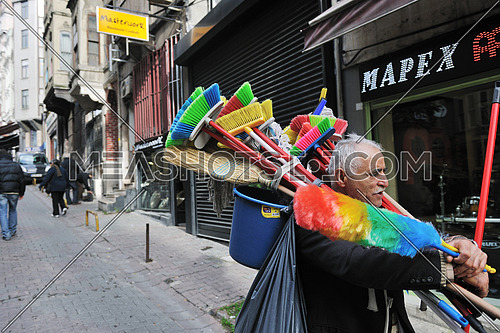 an old man walking in the streets selling brushes and brooms