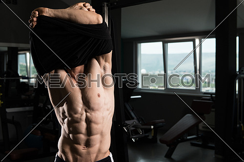 Attractive Bodybuilder Taking His Shirt Off After Training In A Gym