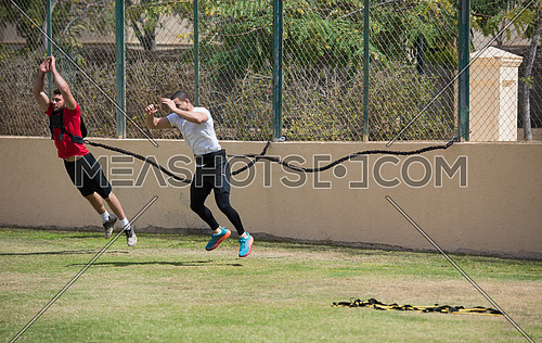 two young middle eastern athletic built men train running on the pitch on a sunny day
