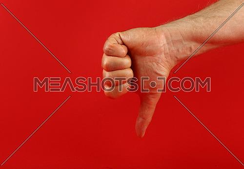 Man hand shoving thumb down, dislike, bad gesture over red background, side view