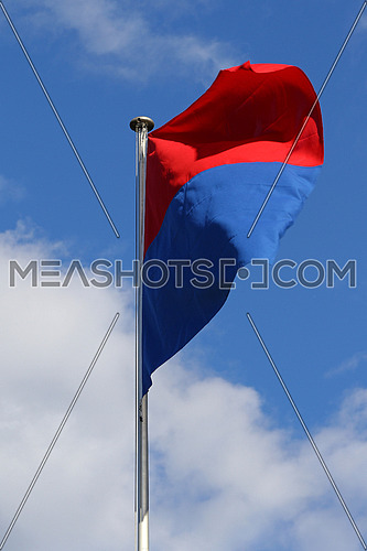 Flag of the State and Republic of Canton Ticino, Switzerland, flapping in the wind against blue skies and white clouds