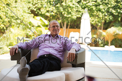 portrait of an elderly middle eastern man to enjoy the sunny summer morning at the pool