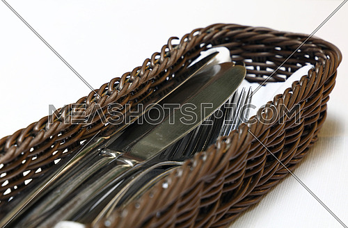 Close up metal dining utensils, forks and knives, in wooden basket container on white tablecloth, high angle view, personal perspective