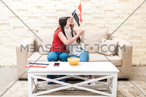 two young ladies hugging eachother on a sofa in front of white table with a mobile phone on and bowl of popcorn, holding two small egyptian flags