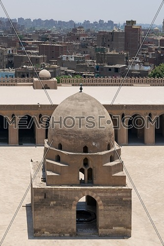 Aerial view of ablution fountain at the courtyard of Ibn Tulun public historical mosque with grunge houses in the background, Old Cairo, Egypt