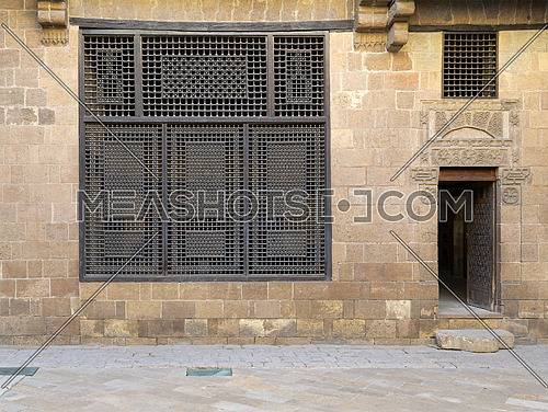 Facade (Mashrabiya window and open wooden door on stone wall) of Beit (house) El Harrawi, an old Mamluk era historic house in Medieval Cairo, Egypt