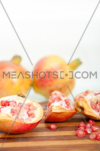 fresh pomegranate fruit on  wood over white background