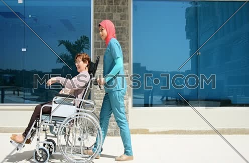 A nurse taking patient for a walk in a wheel chair