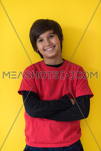 Portrait of a happy young boy in front of colored background