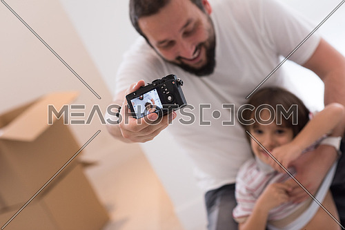 young father and his son photographed themselves with cardboard boxes around them while moving into their new home