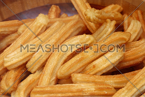 Sweet fresh churros, traditional Spanish or Portuguese deep fried dough pastry snack cooked close up, high angle view