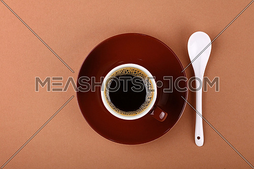 Full small brown ceramic espresso cup of black coffee with saucer and white spoon on paper parchment, close up, elevated top view, directly above