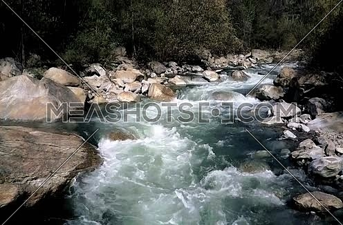 White water river flowing through large rocks in the mountains