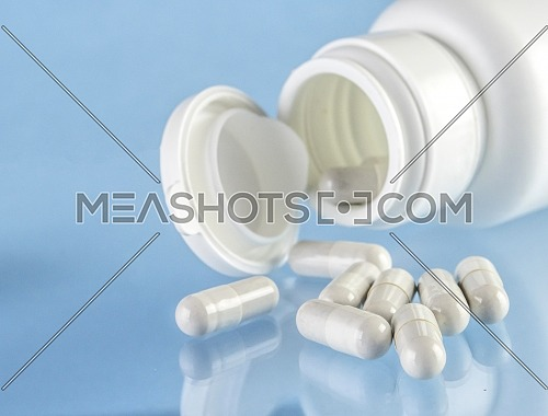 White pills out of a bottle, conceptual image