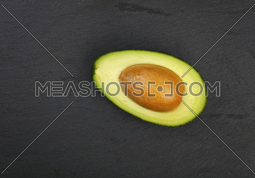 One fresh ripe green avocado half with pit stone on black slate board background, detail, close up, elevated top view