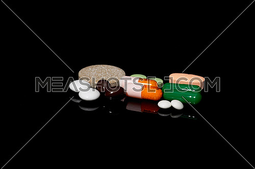 assorted medicine pills on black background with reflections