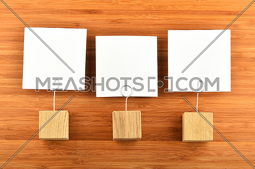 Three white paper notes with wooden holders on bamboo wooden background for presentation