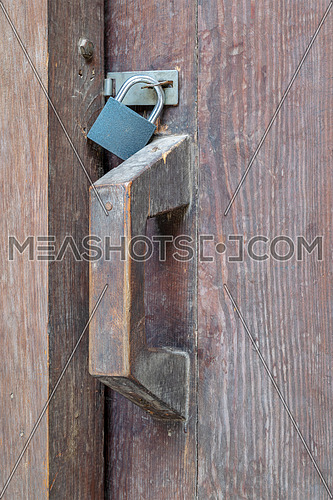 Closeup of a wooden aged latch locked with a padlock in a wooden door