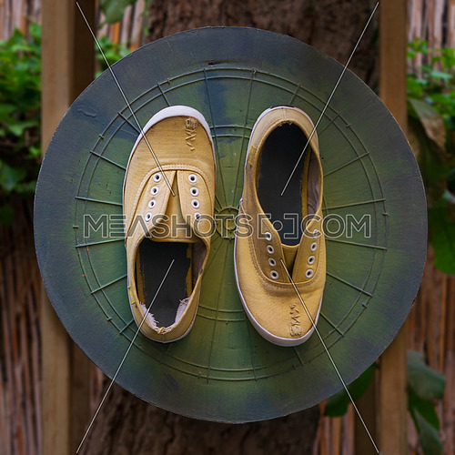 Shabby ruined yellow shoes with stitches attached to grunge green dartboard game board on tree trunk in garden
