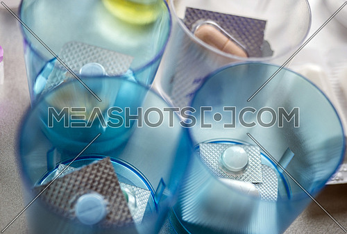 Diverse medication in glasses monodose in hospital, conceptual image, horizontal composition